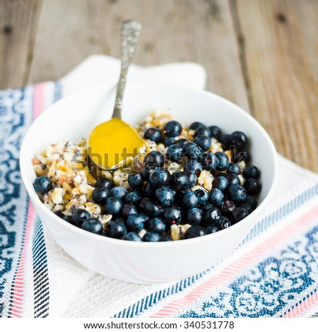 oatmeal with poppy seeds, blueberries and honey, breakfast,clean eating,selective focus - stock photo