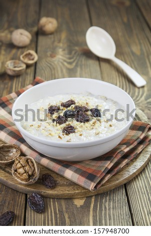 Oatmeal with raisins and walnuts in a bowl on the table