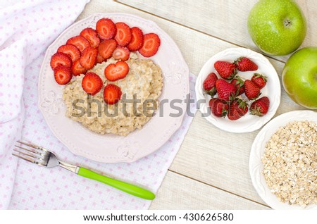 Oatmeal with strawberries and apples on a light table. The view from the top.