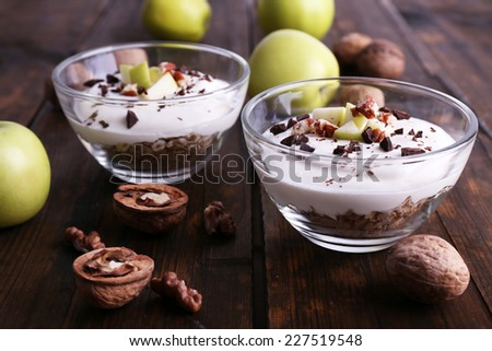 Oatmeal with yogurt in bowls, apples and walnuts on brown wooden background - stock photo