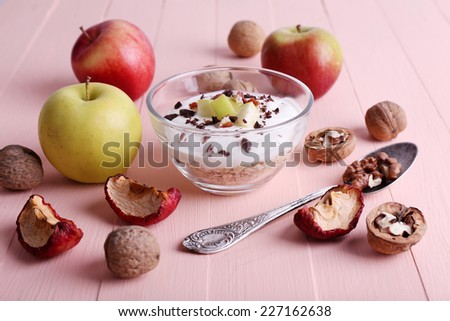 Oatmeal with yogurt in bowls/bowl, apples and walnuts on pink wooden background - stock photo