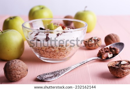 Oatmeal with yogurt in bowls/bowl, apples and walnuts on pink wooden table on light background - stock photo