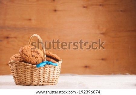 Oats cookies in basket against wood - stock photo