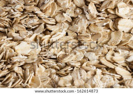 Oats flakes laying on rustic table close up