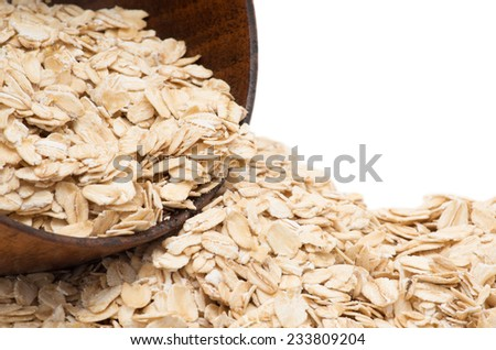 Oats spilling from wooden bowl. - stock photo