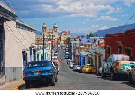 OAXACA, MEXICO - MARCH 18, 2011: Streets of colonial town with cars and Church and former monastery of Santo Domingo de Guzman at the background - stock photo
