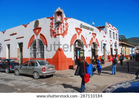 OAXACA, MEXICO - MARCH 18, 2011: Streets of colonial town with cars and people. Burger King in the old colorful building with white and orange walls - stock photo
