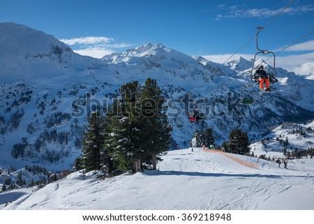 Obertauern, Austria - January 20, 2016: Skiers go down a slope in a ski resort. - stock photo