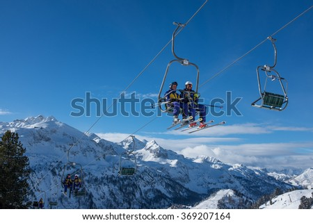 Obertauern, Austria - January 20, 2016: Skiers in a chairlift above a slope in a ski resort. - stock photo