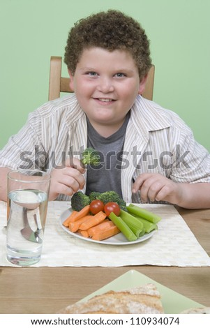 Obese boy having meal together at home