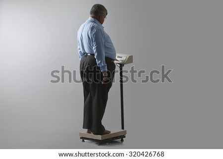 Obese man checking his weight - stock photo
