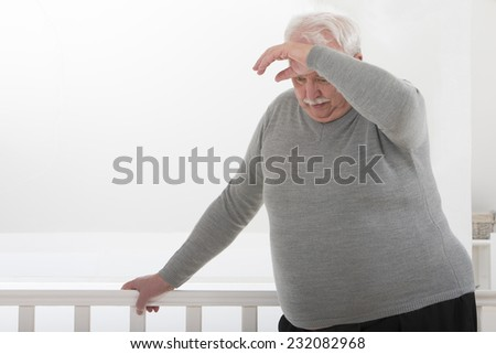 obese man looking worried with hand on forehead - stock photo