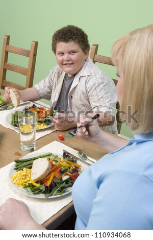 Obese mother and son having meal together - stock photo