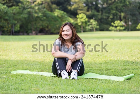 Obese woman relaxing on the grass.