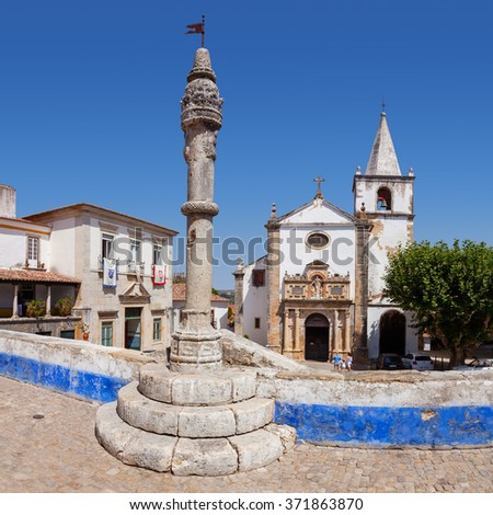 Obidos, Portugal - August, 2015: Medieval Town Pillory and Santa Maria Church seen from Direita Street. Obidos is a medieval town inside walls, and very popular among tourists. - stock photo
