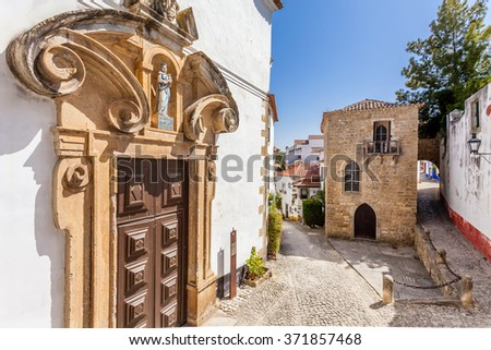 Obidos, Portugal - August, 2015: Misericordia Church portal and the Medieval Sephardic Synagogue in background. Obidos is a medieval town inside walls, and very popular among tourists. - stock photo