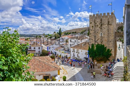Obidos, Portugal - July, 2015: Cityscape of the town with medieval houses, wall and the Albarra tower. Obidos is a medieval town still inside castle walls, and very popular among tourists. - stock photo