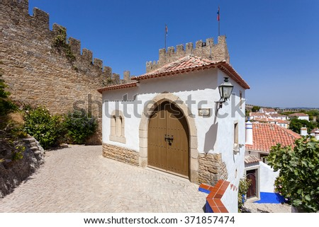 Obidos, Portugal. The medieval Mourisca House. Obidos is a medieval town still inside castle walls, and very popular among tourists. - stock photo