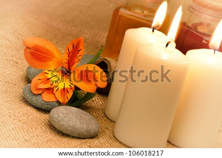 Object for the spa. Candles burning, pebble, a Lily, a bottle with oil.