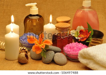 Object for the spa. Candles burning, pebble, a Lily, a bottle with oil, liquid soap, and more. - stock photo