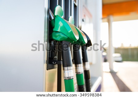 object, fuel, oil, tank and transport concept - close up of gasoline hose at gas station - stock photo