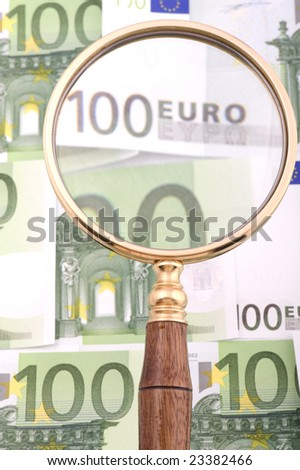 object on white - currency magnifying glass with money