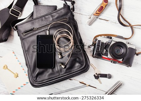 Objects on wooden background: leather bag, camera, smartphone, keys, knife. Outfit of young man. - stock photo