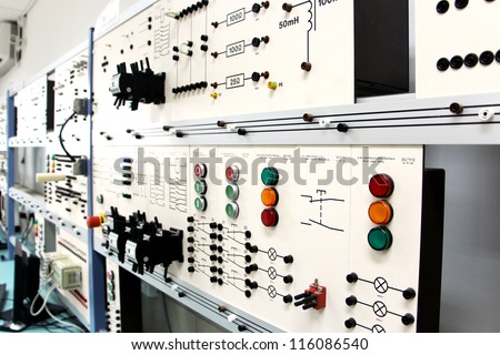 Oblique angle view of a long row of control panels in an electronics lab - stock photo