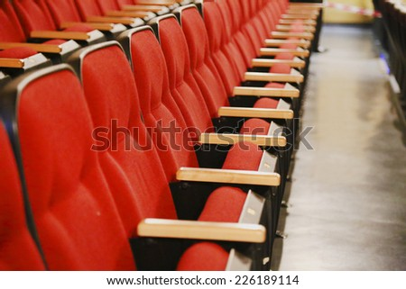Oblique view over a row of red theatre seats at a movie theatre - stock photo