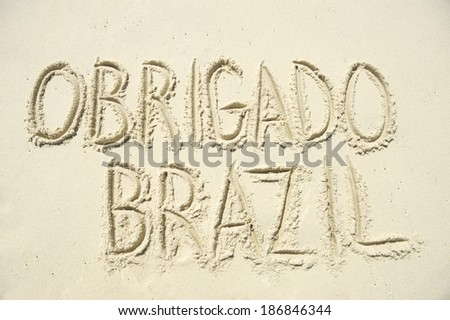 Obrigado Brazil thank you message in Portuguese handwriting in bright sand - stock photo