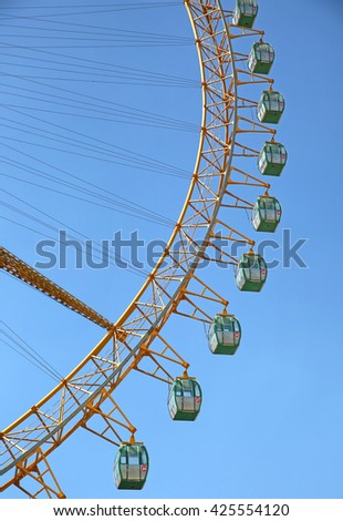 Observation or ferris wheel, against brilliant blue sky.