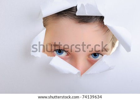 observing eyes of a child in the hole of white paper - stock photo