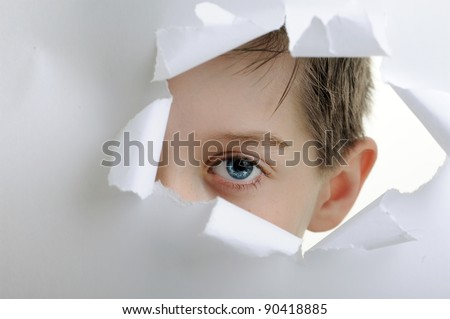 observing eyes of a child in the hole of white paper
