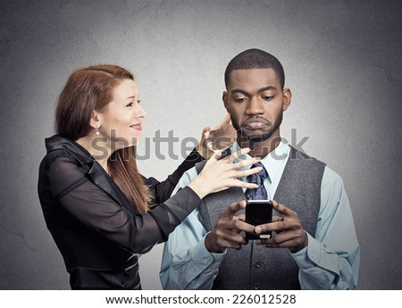 Obsessed with phone work. Attractive woman angry with handsome man who ignores her looking at smart phone reading texting isolated grey wall background. Phone addiction mania concept. Face expression - stock photo