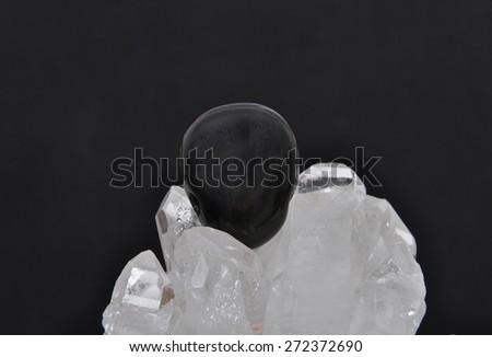 Obsidian on rock crystal - stock photo