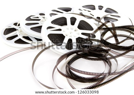 Obsolete rolls of old 8mm movie film are wound on white plastic reels. - stock photo