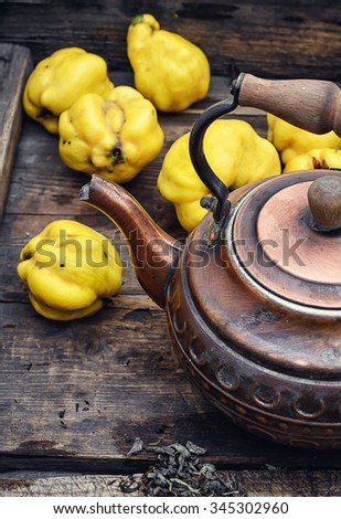 Obsolete wooden box with a stylish copper kettle and fruit quince - stock photo