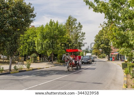 OBZOR, BULGARIA - AUG 10, 2015: Tourists ride on a horse carriage. Architecture and streets of the town of Obzor in Bulgaria. Picture taken during a trip to Bulgaria
