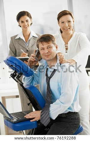 Occupied executive continue working while getting back massage in office.? - stock photo