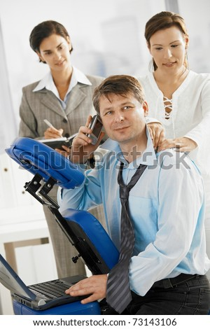 Occupied executive talking on mobile while getting neck massage in office. Secretary making notes the background.? - stock photo