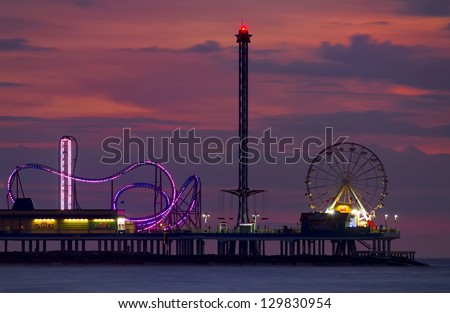 Ocean amusement park rides viewed at dusk