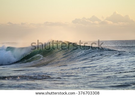 Ocean breaking surfing wave. Pipeline in evening sunset light. Beautiful tropical oceanic background postcard. Big water splashes on seascapes. - stock photo