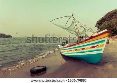 Ocean coast landscape with traditional Indian boat and chinese fishing nets at Cochin (Kochi). South India, Kerala, Kochin - stock photo