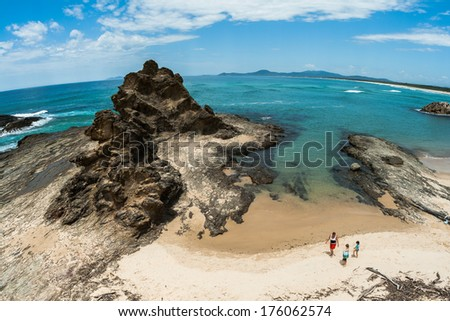Ocean coastline beach with rocky headland landmark into blue waters with family standing on beach nearby shallow tidal cove  - stock photo