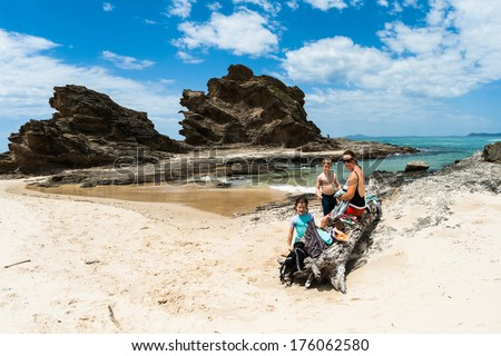 Ocean coastline beach with rocky headland landmark into blue waters with  Mother Son Daughter finished swimming in shallow tidal cove  - stock photo