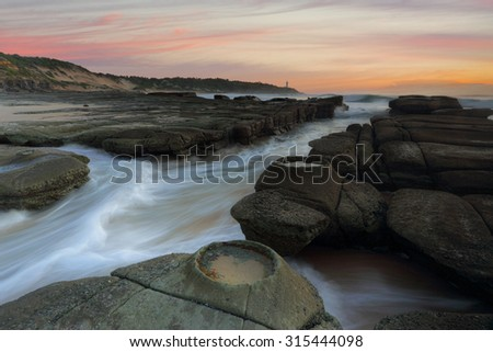 Ocean flowing in and out of the rock chasm at Soldiers Point Norah Head - stock photo