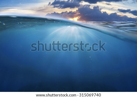 ocean half water with sunset sky - stock photo