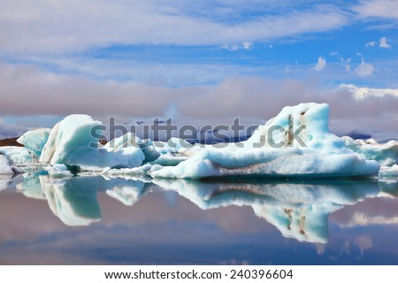 Ocean ice lagoon Yokulsarlon. Icebergs and ice floes are reflected in smooth water. Iceland in July - stock photo
