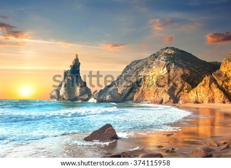 Ocean Landscape at Sundown, big rocks and stones beach. Portugal, Europe - stock photo