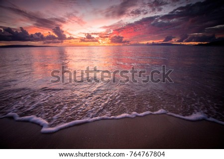 Ocean lapping sand at sunset